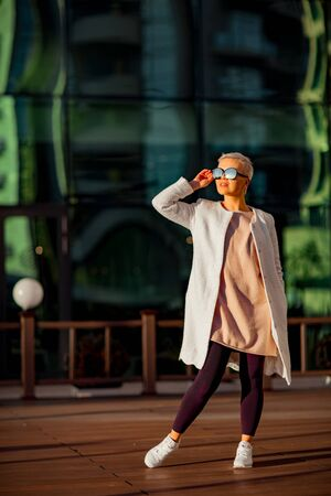 Junge Frau, blond, geht mit Sonnenbrille