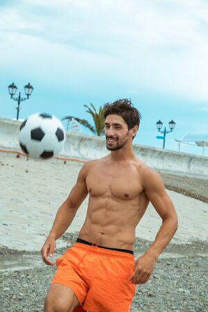 sporty, sexy dark-haired man in orange shorts, playing football on the beach Stock Photo