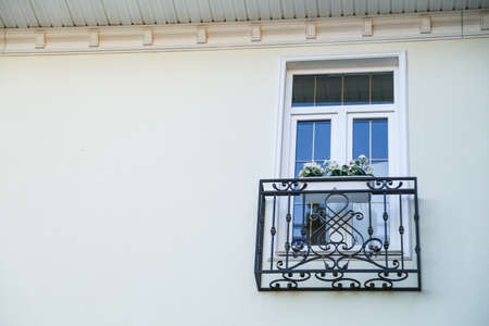 white window with black wrought-iron sill, on the wall of the house