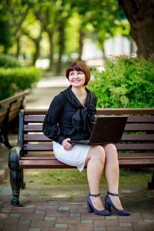 portrait of a beautiful business woman in a black shirt with a laptop, in a Park on a bench Stok Fotoğraf - 154202547
