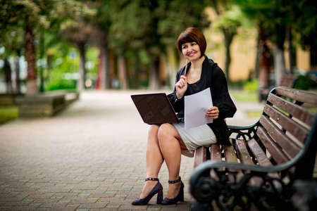 portrait of a beautiful business woman in a black shirt with a laptop, in a Park on a bench