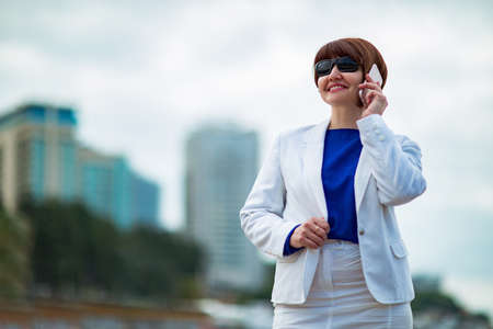 A beautiful woman, brown-haired, in a white business suit and blue blouse,with documents in her hands, stands against the background of the city near the sea, a Business portrait . Reklamní fotografie