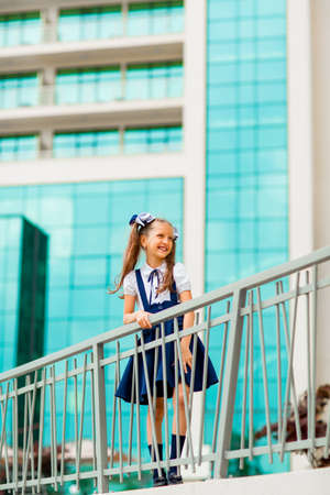 A schoolgirl in a blue school uniform, standing in the background of the school, with glass walls.