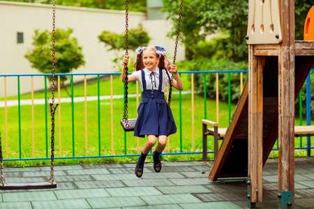 schoolgirl in school uniform, swinging on a swing in a children's amusement Park Foto de archivo