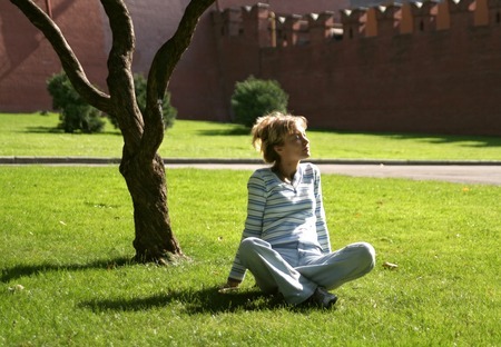 The girl having a rest on a grass about the Kremlin wall in Moscow Stock Photo