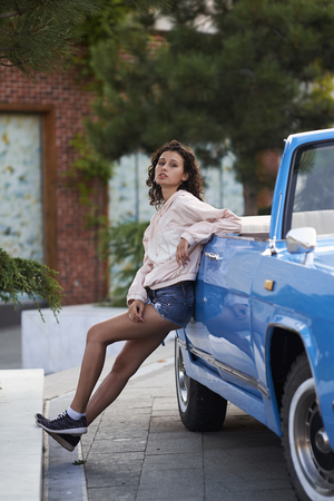 Beautiful curly girl in shorts and blue retro cabriolet