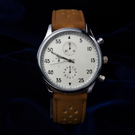 wrist strap: Mens wrist watch with brown leather strap closeup on a dark blue background Stock Photo
