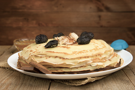 matting: Pancakes with berries, fruits, chocolate, pine nuts and honey on white plate on a natural wooden board