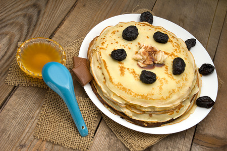 Pancakes with berries, fruits, chocolate, pine nuts and honey on white plate on a natural wooden board