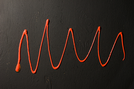 Abstract background. Red acrylic paint on a black wooden background