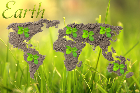 Earth Day. Concept ecology. World map, globe from the soil with green plants around the world on natural background