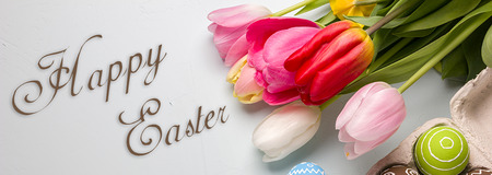 Painted easter eggs and bouquet of spring tulips closeup on a light blue background with space for congratulation, border design panoramic banner