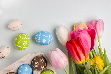 quail: Painted easter eggs and bouquet of spring tulips closeup on a light blue background with space for congratulation Foto de archivo