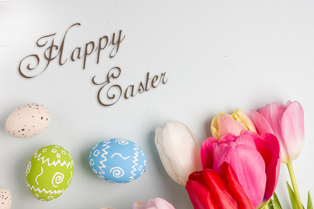 huevos de codorniz: Painted easter eggs and bouquet of spring tulips closeup on a light blue background with space for congratulation Foto de archivo