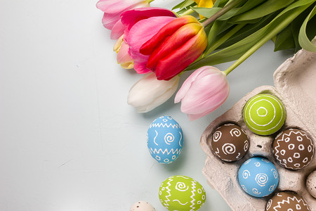 Painted easter eggs and bouquet of spring tulips closeup on a light blue background with space for congratulation Stock Photo