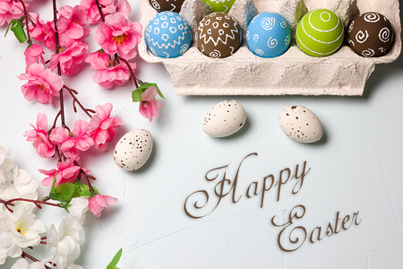 Painted easter eggs and branches of spring sakura closeup on a light blue background with space for congratulation Stock Photo