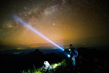 Jonge man die op de berg met nachtelijke hemel Stockfoto