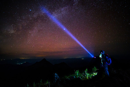 astrophysics: Young man Standing on Mountain with night sky