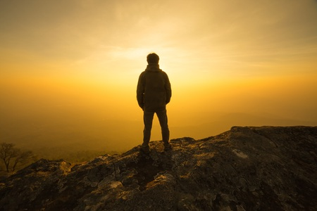 silhouette man standing into sunset sky