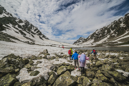 Group of mountaineers walking trough the mountains covered with stone