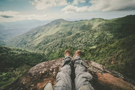 view on sea: Legs of a man sitting on the edge of a cliff in the beautiful mountains Stock Photo