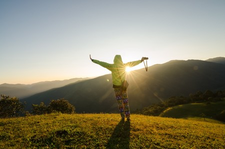 against the sun: freedom girl with hands up in the mountains against sun