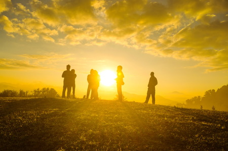 enjoyment: Group Of People relaxing on field with sunrise