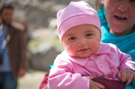 HUNZA, PAKISTAN - APRIL 14: An unidentified woman and baby in a village of the Hunza, April 14, 2015 in Hunza, Pakistan with a population of more than 150 million people.