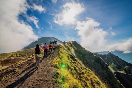 Groep wandelaars aflopend op broze bodem in de krater van de vulkaan van Batur. Bali, Indonesië Stockfoto