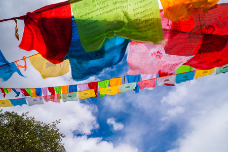 Prayer flags on snow mountains at Yading Nature Reserve, China. Stock Photo