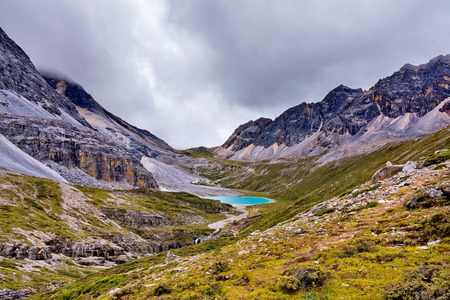 jokul: Milk lake on the snow mountains with clouds and sky in Yading, China. Stock Photo