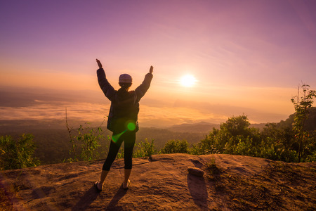 Happy Young Woman Hiker With Open Arms Raised at Sunset on Mountain Peak Stock Photo