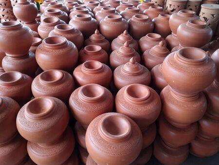 open air workshop of ceramics, earthenware, orange and brown terracotta flower pots craftmanship in Thailand