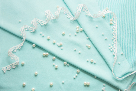 the thread, the beads, the lace are on the turquoise background Stock Photo