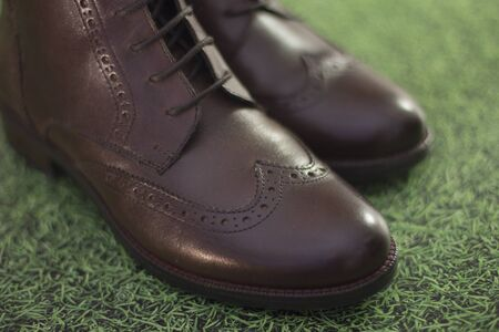 new genuine leather shoes with a pattern. new brown leather shoes with laces on a dark background