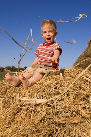 hayrick: barefooted  boy sit on a hayrick and throw a straw
