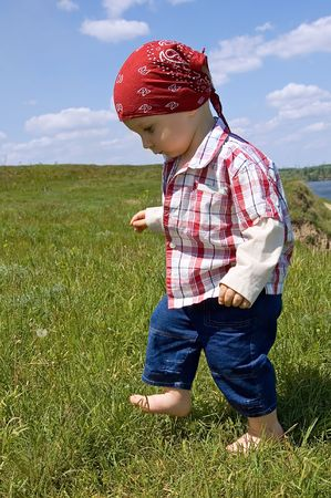 1,5 years old barefooted  boy to step out briskly against summer landscape photo