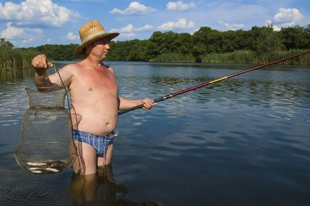 fisherman holding fishing-rod, standing in water Stock Photo - 2834273