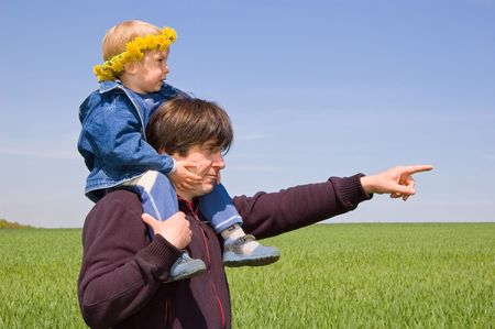 father point the way with his hand to his little son against spring meadow Stock Photo - 2920374