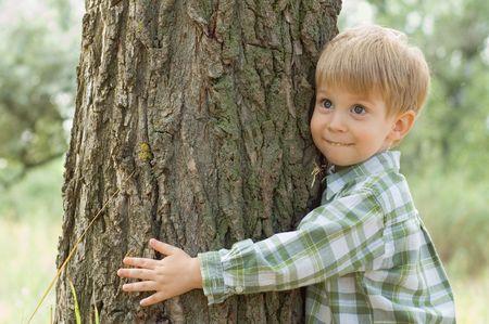 cuidado de la naturaleza - muchachito abrazar un �rbol  Foto de archivo - 3379700