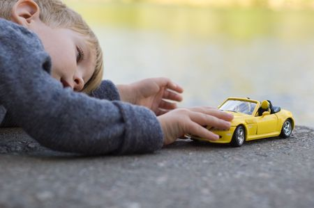 serenity: little boy play with a car outdoor
