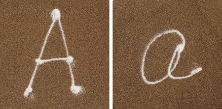 A - white alphabet written in brown sand  Stock Photo - 4907673