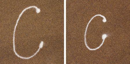 versatile: C - white alphabet written in brown sand