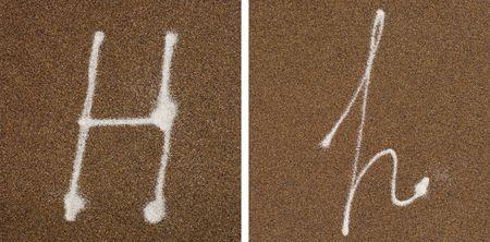 versatile: H - white alphabet written in brown sand