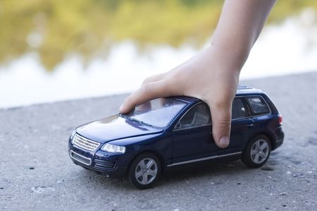 close-up of a child hand playing with car outdoor photo