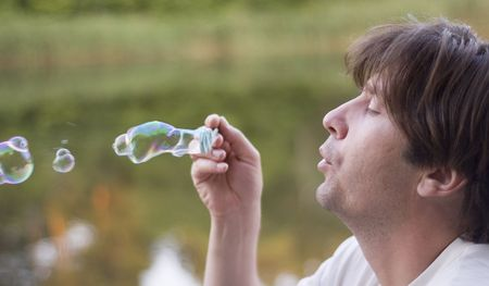 man blowing soap-bubbles on nature background photo