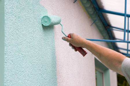 handtools: painting wall with a roll in green outdoor Stock Photo