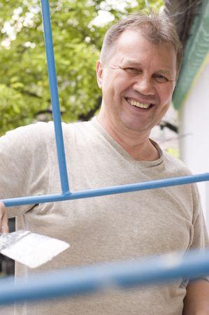 happy man makes renovation outdoor photo