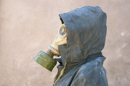 man in gas mask and dirty waterproof cape-tent with hood against cement wall photo