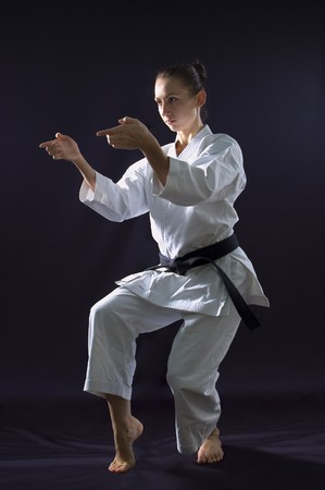 martial arts woman: karateka girl on black background studio shot